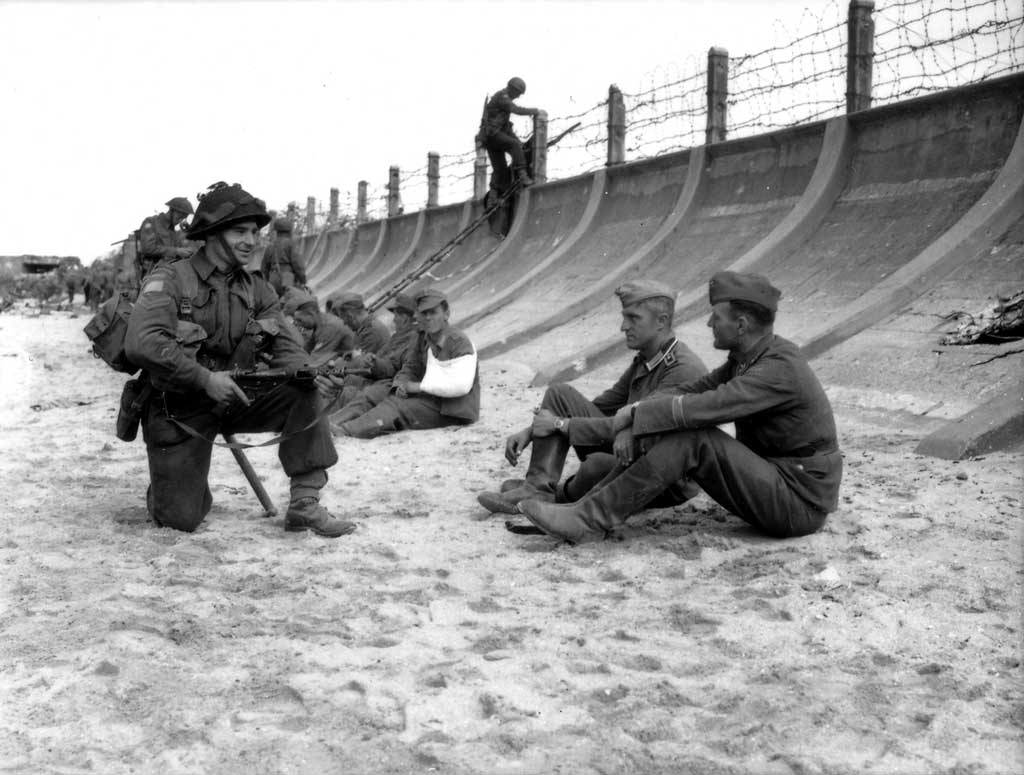 1944, France, Normandie, Juno Beach, Des POWs allemands sous la garde de soldats canadiens le D-Day